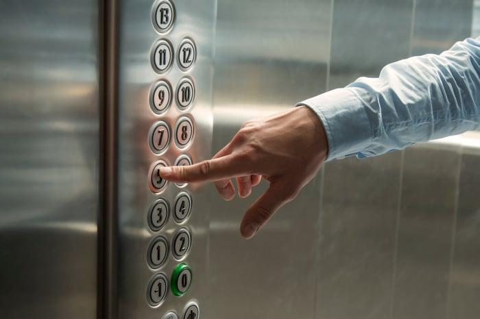 Finger pressing an elevator button