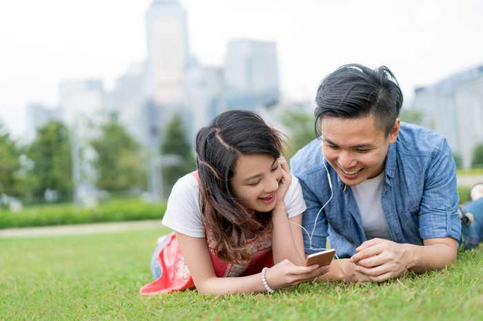 A man and woman lie on the grass with earplugs in their ears, looking at a smartphone.