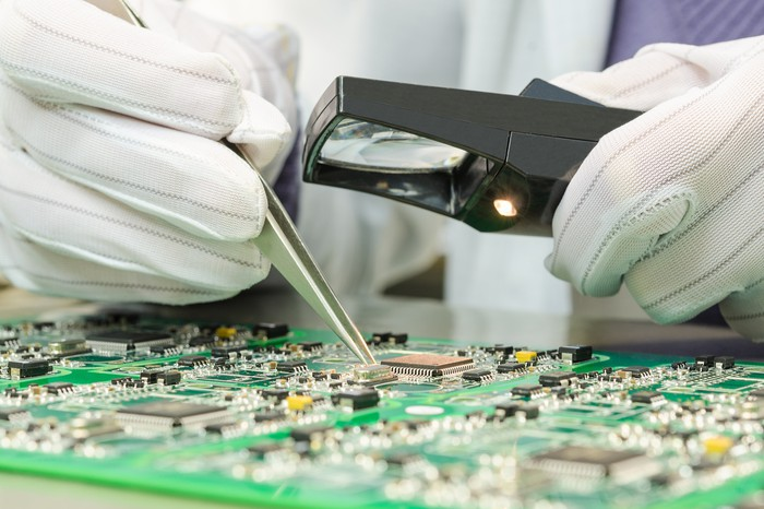 A semiconductor technician solders a chip using a special magnifying glass.