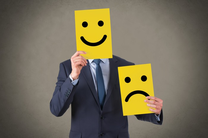 A person holding up a smiley face.
