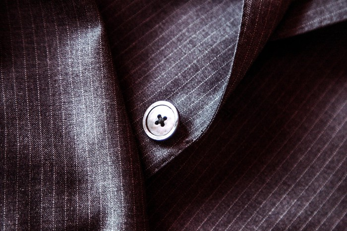 close up of detail of suit, featuring button