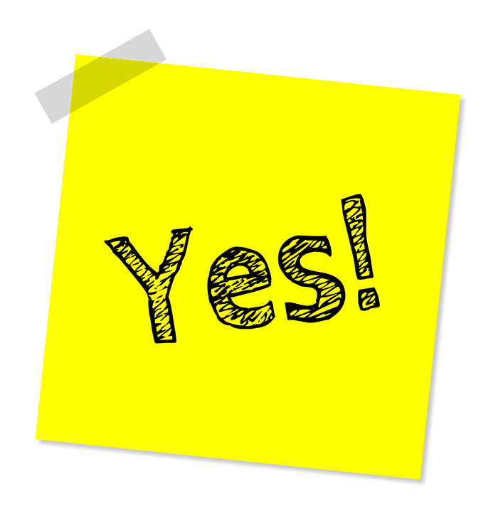 "Yellow sticky note that says ""Yes!"" taped to a surface"