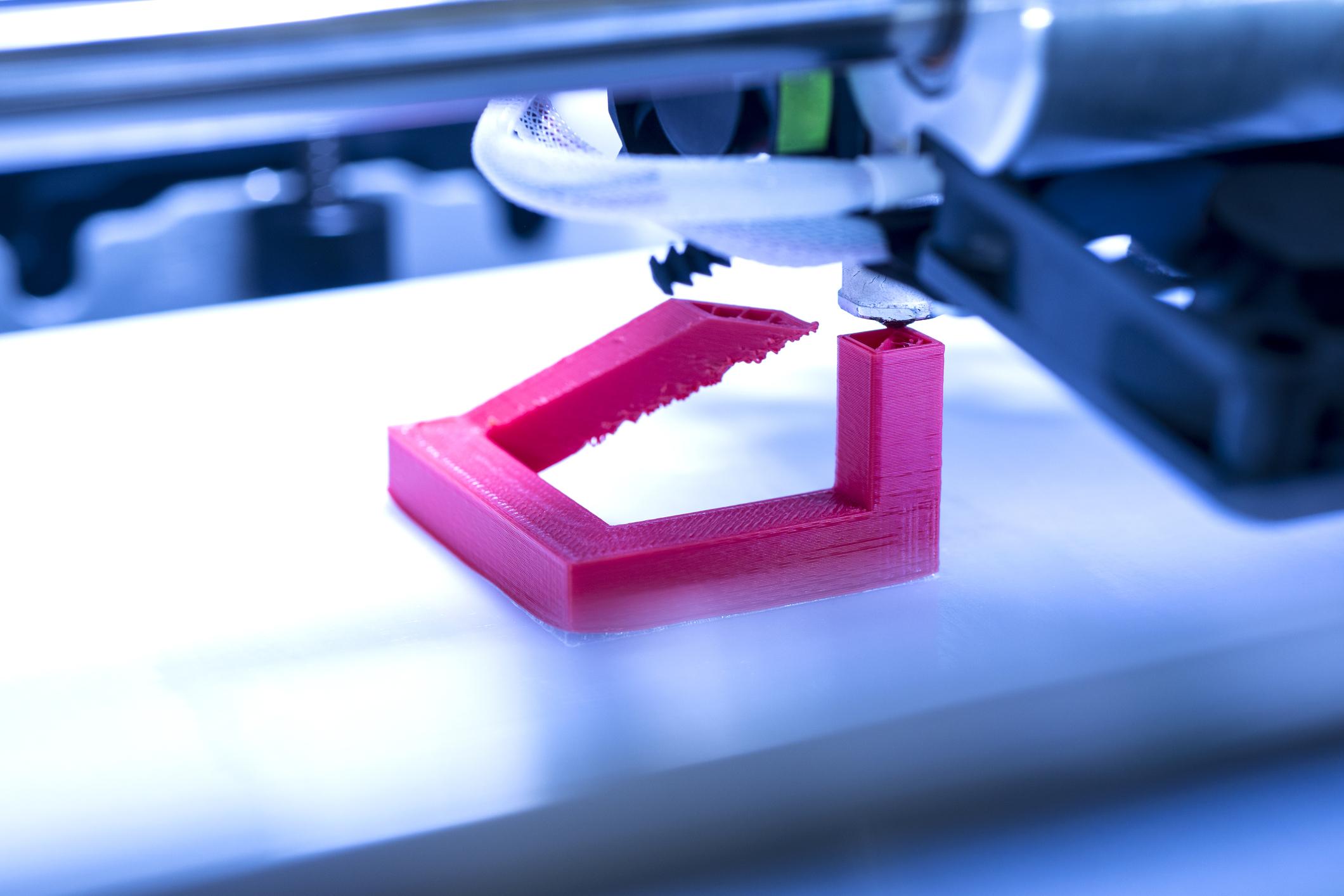A 3D printer printing a magenta-colored part.