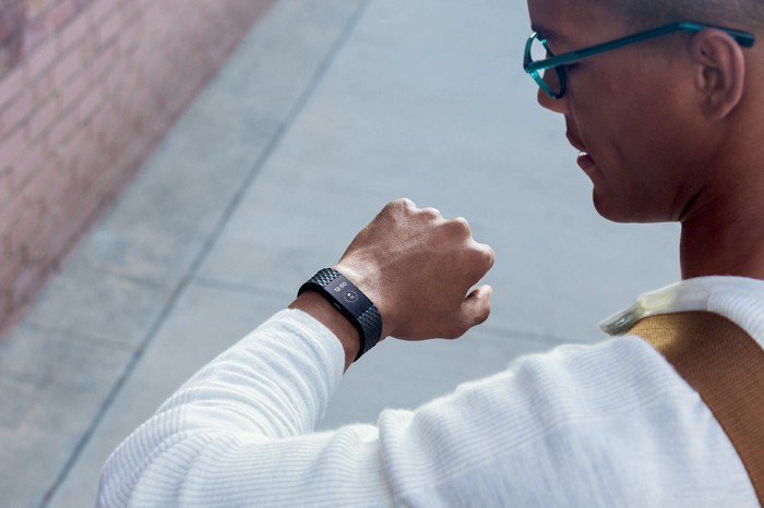 Casually dressed man checking the time on the  Fitbit on his wrist.