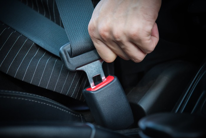 Hand fastening seat belt in the car.