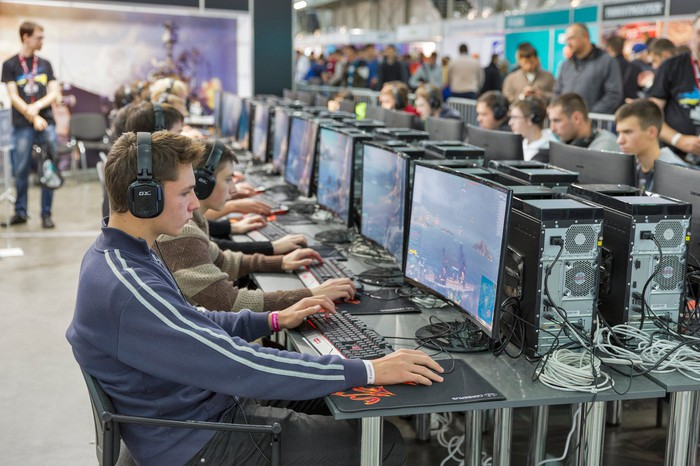 A room filled with people playing PC games.