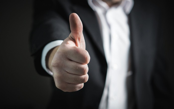 Torso of man in suit, with hand outstretched, giving thumbs up