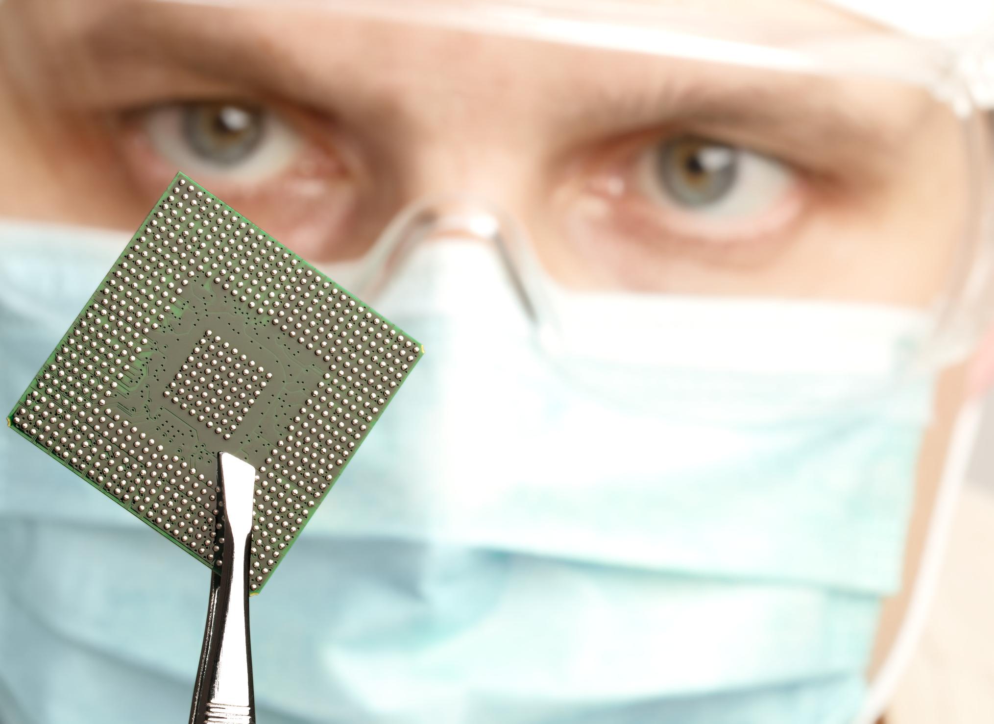 Man holding a microchip in tweezers.
