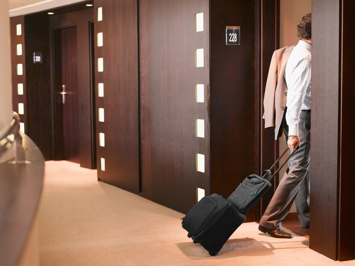 A man entering a hotel room pulling his luggage behind him.
