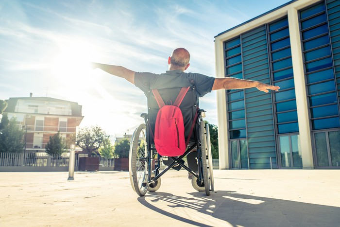 A man in a wheelchair outside of a building raises his arms vertically as if to fly.