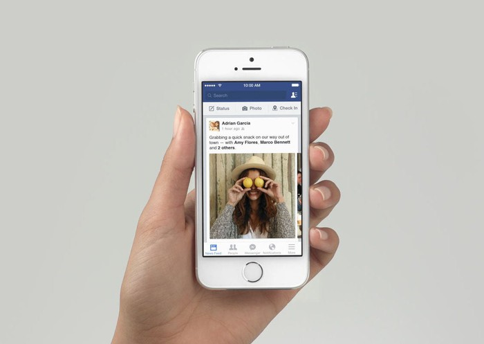 A hand holding up an iPhone displaying a Facebook newsfeed.