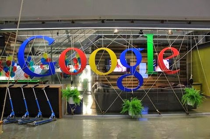 Scooters lined up in front of Google's logo in one of its office buildings.