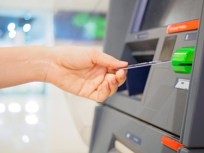 Colorful close-up of hand feeding card into ATM machine.
