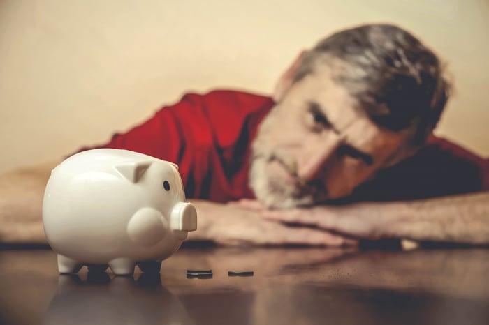 A senior man sadly staring at his empty piggy bank.
