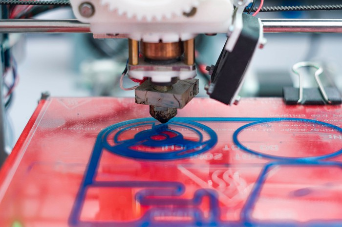 A close-up of a 3D printer just beginning to print a yet unrecognizable object.