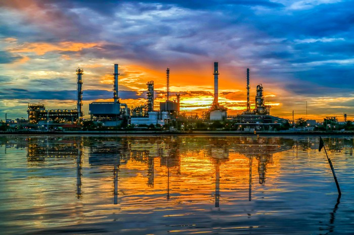 An oil refinery at twilight reflected in the water.