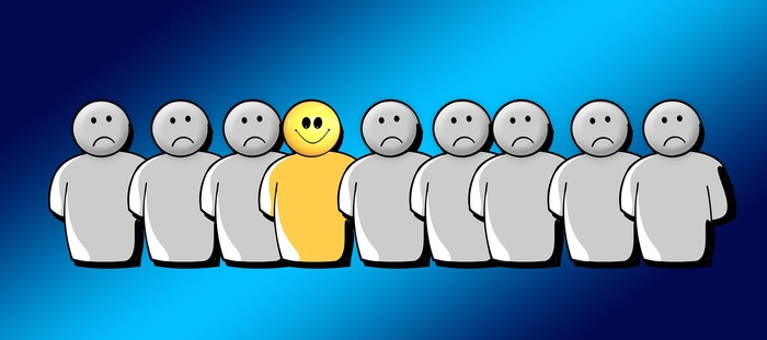 Cartoonish graphic of a row of people all frowning, except the smiling person in the middle