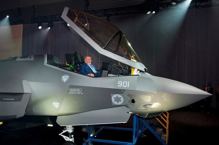 Israel's minister of defense smiling from the open cockpit of an F-35 on display.