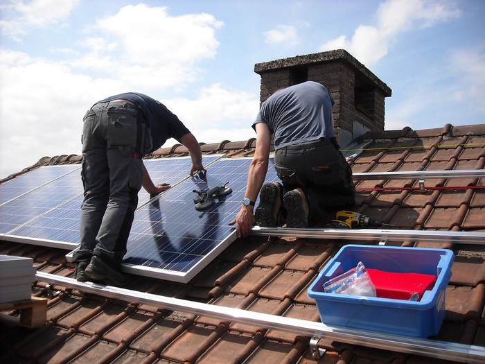 Workers installing solar panels on a residential roof.