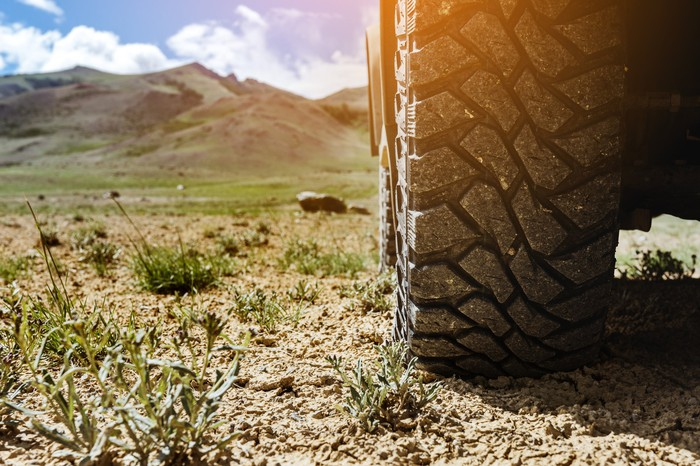 Truck tire in foreground of dirt road