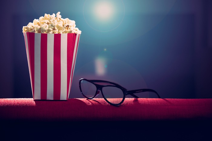 Popcorn and glasses with a movie projector in the background.
