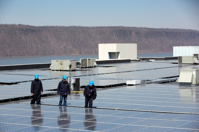 Workers looking at solar field.