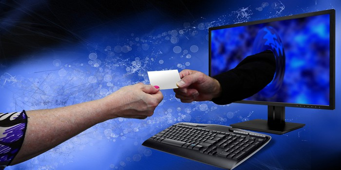 Two hands, one coming through a computer monitor, hold opposite ends of a slip of paper.