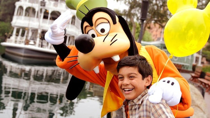 Boy with Goofy character in front of Mark Twain Riverboat ride at Disneyland.