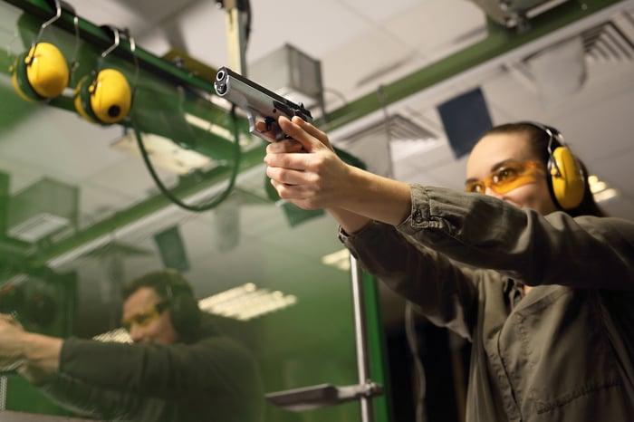 A woman takes target practice at a gun range.