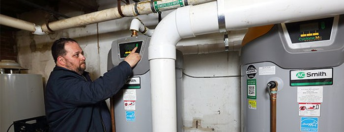 Man installing commercial water heating system