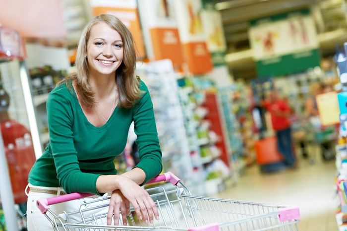 Woman leaning on shopping cart in big box store