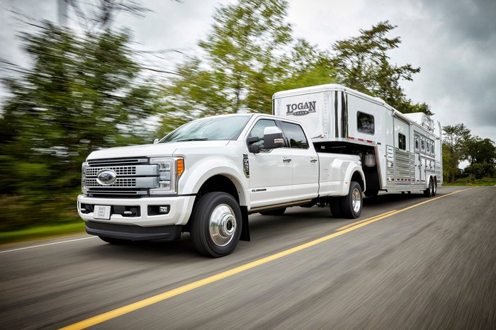 A white Ford F-450 pickup pulling a big trailer.