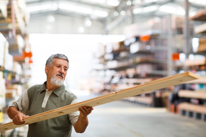 A man inspects a piece of lumber at a home improvement store.