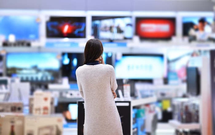 Woman looking at a row of TVs in an appliance store.