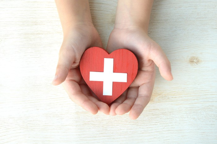 Two outstretched hands hold a small plastic heart toy with a white cross medical symbol painted on it.