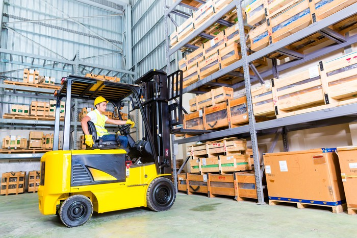 Forklift in a warehouse picking boxes.