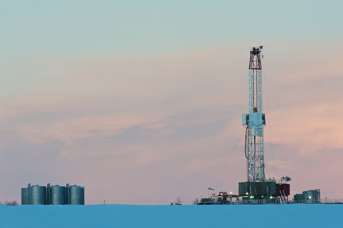A natural gas drilling rig at dawn in a snowy field.