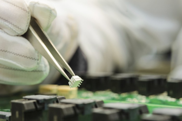 A gloved worker installs a chip onto a circuit board.