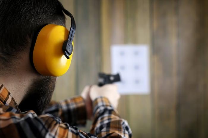 A man points a gun at a target at a shooting range.