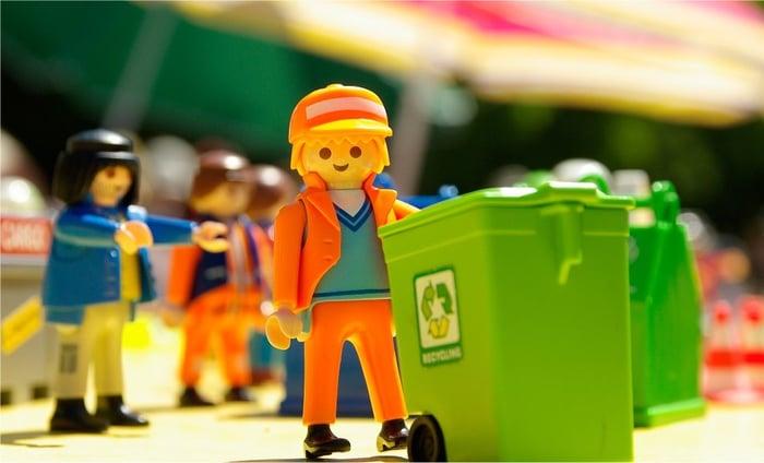 A Lego figure pushing a recycling bin.