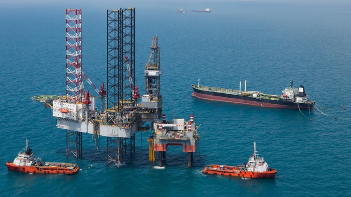 Jack up rig with support vessels.