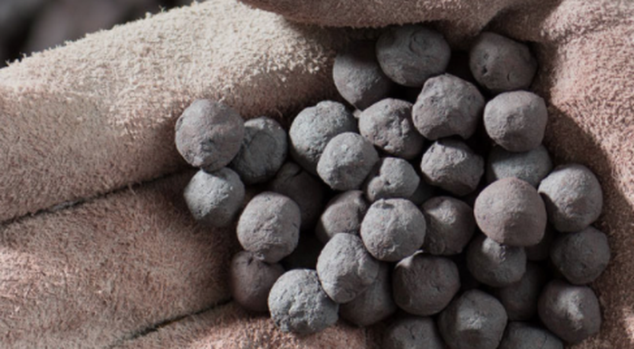 Iron ore pellets in a glove.