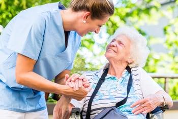 Caregiver_tending_to_elderly_woman