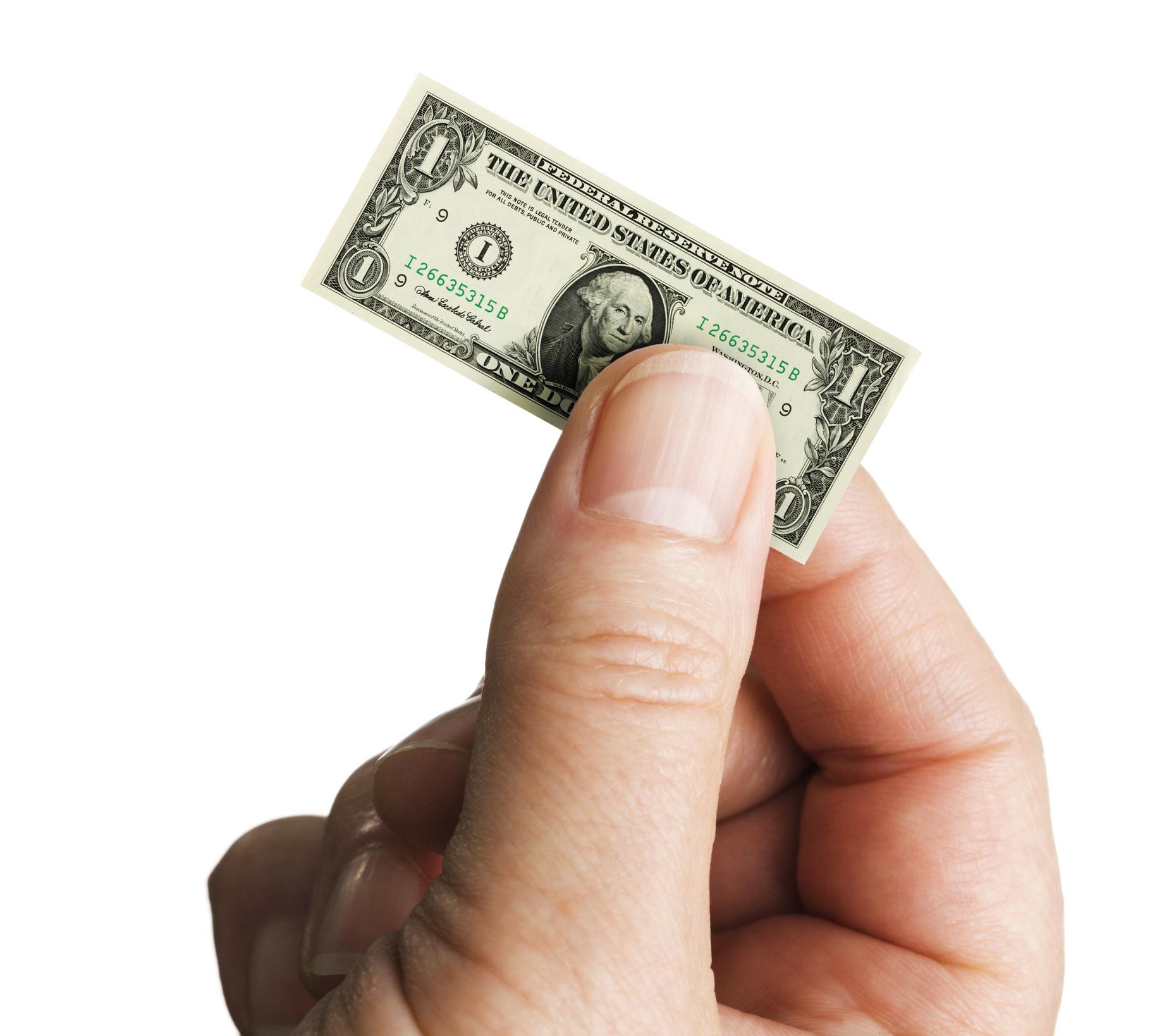 Tiny shrunken dollar held in fingers