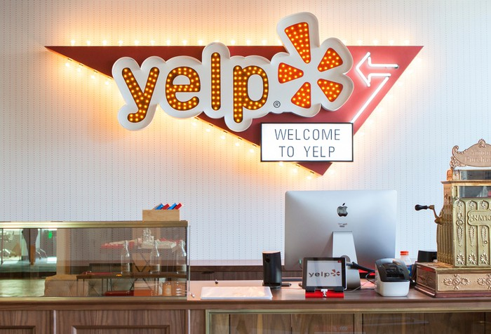 A Yelp office desk, with a lighted Yelp sign on the wall.
