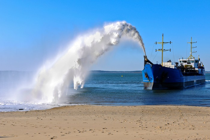 Dredging ship spraying sand onto shore.