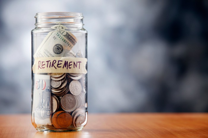 """Glass jar with cash in it, labeled """"retirement"""""""