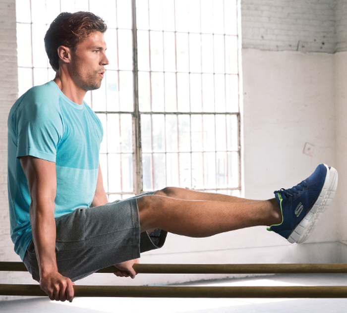 Athletic male dressed in workout clothes on parallel bars with Skechers sneakers.