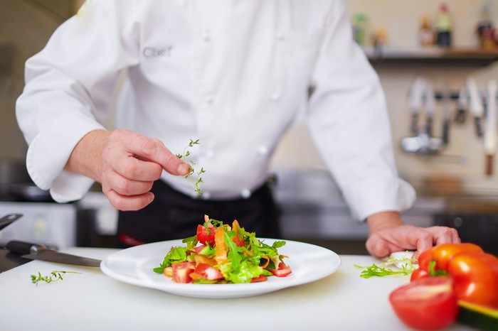 A chef adding herbs to a salad.