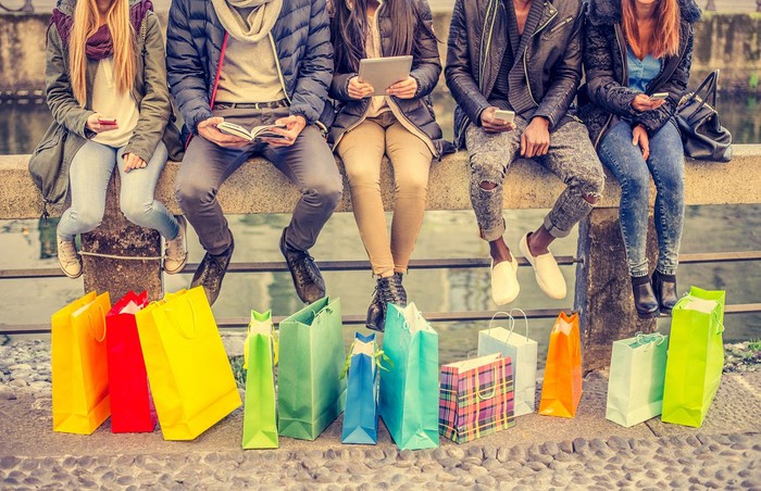 Five people sitting on a bridge with shopping bags nearby